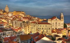 Telgraph Lisbon city break guide check out the century-old wooden trams & iron funiculars that lurch & rumble their way among the 7 steep hills over which this city lies, wander through Baixa district, where age-old herbalists, haberdashers & tailors rub shoulders in baroque streets of the ornate city centre, Meander up a lofty hill to Moorish Alfama neighbour­hood, where sunset-amber walls and dusty lanes orbit the Arabic-medieval castle looming, omnipresent, over the terracotta rooftops…