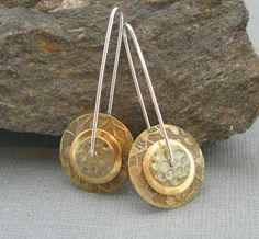 These earrings sport 3 layers of brass discs, each with its own texture, and then domed for dimension. They hang like pinwheels - and yes, they spin - from a hand formed sterling wire with a secure lock closure. Great look and fun! 1 3/4 inches long x 5/8 inch diameter.