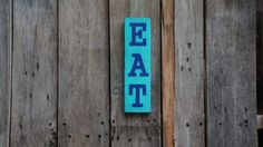 This is one pallet board that has been cut, sanded painted and distressed. The board is painted aqua with EAT in blue. The dimensions are 10 in by 2.75 in. This has a hook on the back for hanging. ****All pallet art can also be customized with any color or design. If you dont see what you are looking for, message me to have a custom order made for you!! All pallet art is hand painted. Every item can be duplicated but keep in mind each board is different and the end results may be a little…
