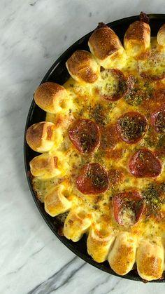 Receita com instruções em vídeo: Agora você pode fazer a famosa pizza cheesy pop em casa!       Ingredientes: 6g de fermento biológico seco, 1 colher de chá de azeite de oliva, ¾ de xícara de água, ¼ de xícara de leite, 1 pitada de açúcar, 2 ½  xícaras de farinha de trigo , 1 pitada de sal, 2 colheres de sopa de extrato de tomate, 150g de queijo muçarela  ralado, 100g de pepperoni, Orégano, 200g de queijo muçarela em bastão, 1 gema para pincelar