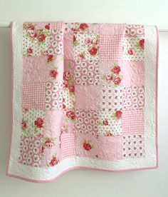 This adorable pink baby girl quilt is made of soft cotton floral fabrics. The backing and binding are made with coordinating prints. This quilt measures 41 x 47, the perfect size for a crib quilt and snuggling with your little one. It would make a lovely accent piece for a little girls room.  This beautiful quilt was pieced and longarm quilted in my studio. The extensive quilting fills the lovely pink prints with roses. The binding is double folded with mitered corners and machine stitched…