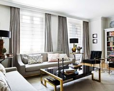 gray drapes, gray couch, black and gold coffee table, black lamp shades