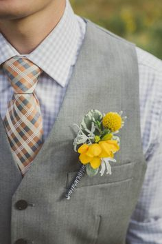 Yellow boutonniere on a grey vest; No need to wear a jacket if you're not comfortable in one