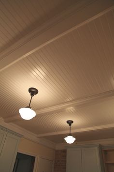 Finished beadboard paneled ceiling w/ bronze finished school house pendant fixtures in kitchen.