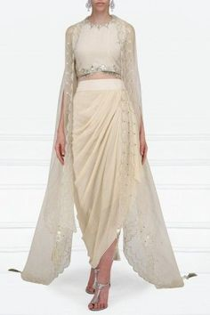 Priyanka Singh Featuring a beige crop top in georgette base with pearls, sequins and stones hand embroidery. It is paired with a matching drape skirt in crepe base and an asymmetrical embroidered organza cape with scallop edging. Indian Designer Outfits, Designer Dresses, Drape Skirt Pattern, Skirt Fashion, Fashion Dresses, Mehendi Outfits, Indian Gowns Dresses, Draped Skirt, Dress Indian Style