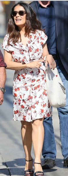 Who made Salma Hayek's print white dress, hobo handbag, and blue wedge sandals?
