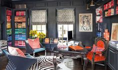 """This might not look like the typical man cave, but according to Kourtney, it's """"pretty much Scott's room."""" To add a bit of sentiment, Kourtney had her father's old desk refinished for the space and filled it with books that belonged to her parents. The meticulous process of removing the book covers and color coding them is a project that Kourtney tackled herself!  Photo by Grey Crawford for Jeff Andrews"""