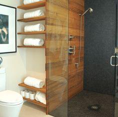 Idea bagno moderno con pavimento e rivestimento della doccia in mosaico nero - muro e mensole in legno - piatto doccia a filo pavimento
