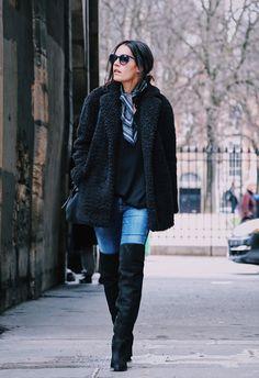 Street style look com calça jeans, bota over the knee, maxi casaco preto pêlos e óculos preto.
