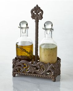 "Handcrafted oil and vinegar set. Cast aluminum and glass. Hand-painted finish. Set includes caddy and two bottles. 8.5""W x 3.75""D x 13""T. Glass bottles, dishwasher safe; caddy, hand wash. Imported."