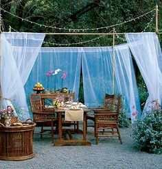 An outdoor room made up of a table and mosquito net walls.  Love that the poles are held up by big flower pots.