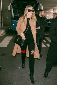Yes. Gigi loves black leggings. To change things up at the airport, she opted to go for a style with cheeky patches, a heart and star, around the knees, pairing the statement bottoms with a long-sleeved black top, leather boots, and a sumptuous camel coat.