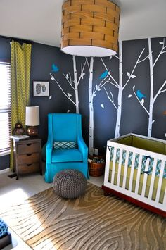 This retro nursery is so naturally cool with the dark blue walls and the birds and tree decals. #nurseryideas #retronursery #brownrug