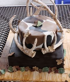 Camouflage Cake - The cakes are covered in MMF, chocolate on bottom and regular on top.  The antlers are made with gumpaste covering a copper tubing skeleton, and the leaf accents are MMF cutouts.  Thanks!