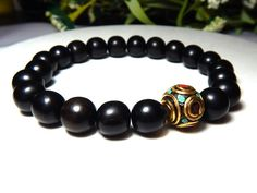 About the Bracelet An interesting turquoise and red handmade focal bead from Nepal. This beautiful bead is surrounded by rich dark ebony wood. A light weight and comfortable mens bracelet. Bracelet De