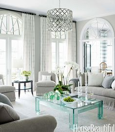 A 1980s Lucite-and-glass table provides a jewellike accent to the muted tones of the living room. Asilah chandelier, Jerry Pair.   - HouseBeautiful.com