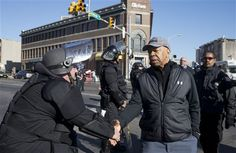 Congressman Elijah Cummings in Baltimore shaking a State Trooper's hand after the riots