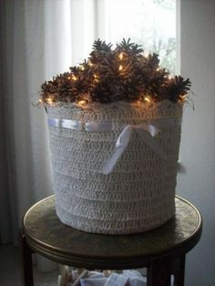 Make the basket out of burlap and fill with pine cones and white lights