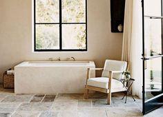 Sandsteinplatten wie aus einem alten Schloss, eine Wanne mit Natursteinverkleidung und ein rustikaler Korb mit weichem Frottier. Abgerundet wird das Lagom-Bad-Szenario mit einem einfachen Polstersessel. Mehr braucht es nicht fürs Urlaubsfeeling. Fast ist man gar versucht zu sagen: ein Bad für die Ewigkeit. Foto: vogue.com