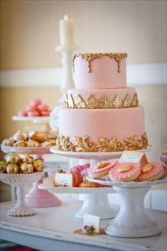 Lovely pink cake with antique gold trim and various little pink treats arranged on pedestal stands!