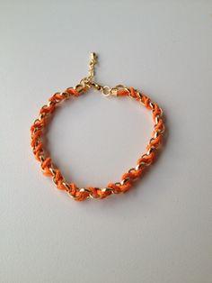 chain bracelet with orange string pulseira de corrente dourada trançada com fio laranja
