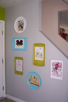 Spray-painted cookie sheets hung on the wall. Use magnets to display artwork.  Easy to swap out! Brilliant.