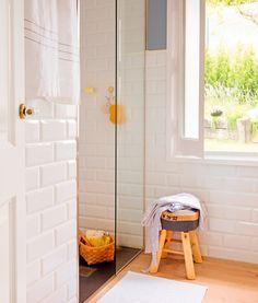 Baño con suelo de parquet, paredes revestidas con azulejos balncos, taburete vintage y cesta con asa