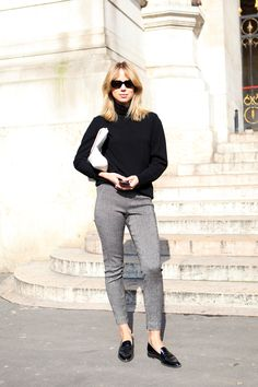 Black Super sunglasses, black knit turtleneck, white leather satchel worn as clutch, cropped grey trousers and patent black loafers. Elin Kling