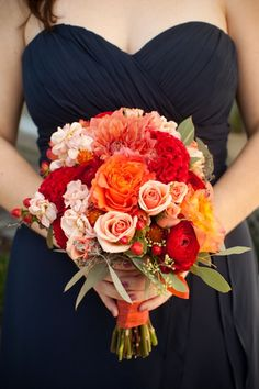 a bouquet full of orange, reds, and pinks. totally works with the navy blue bridesmaid dresses. Photo by Holly Chapple Flowers
