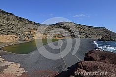 Green Lagoon, el Golfo, Laguna Verde - Lago de los Clicos - on Lanzarote , Canary Islands. Red, yellow and brown rocks with a gren lake on the lack beach contrasted with a blue water of the Atlantic Ocean.