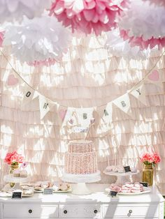 Pretty baby shower dessert table with pink ruffle backdrop