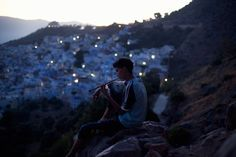 A young man smokes and relaxes at dusk in the Rif Mountains in Chefchaouen. The Rif Mountains are known as one of the largest cannabis-producing regions in the world. While the harvest is mainly used to make hashish for export to Europe, many locals smoke a fine powder called kifi, made of the leftover flowers and stems.