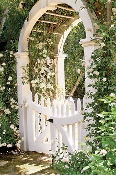 For a majestic garden gate, try a white barreled archway. This gate's arbor reaches an impressive 14 feet, and is twined with Iceberg and Cécile Brunner roses. #gardengates