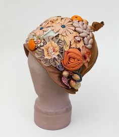The milliner pulled out all the stops with the exuberant embellishment. Plump padded fruits are mixed with stylized beaded silk flowers and cellophane-type leaves. The fun loving style personifies the joyful mood of the 1920s.