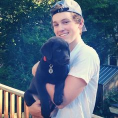 cute kid with black lab puppy