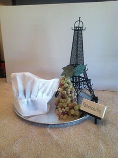 RATATOUILLE CENTERPIECE: Got the eiffel tower, the base, & the fake grapes at an Arts & Crafts Store. Got the Chef's hat from a party store. Then, I printed a picture of Remy from the Ratatouille movie, traced the image on black board, & used an exact knife to cut him out. Taped him to the inside of the hat. Added a fake tea light candle inside and turned it on during reception. Had a very tasty effect;)