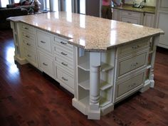Large Kitchen Island, featuring open corner shelves with decorative posts. The 2 deep drawers in the middle are Sub-Zero fridge drawers. Note the electrical outlet hidden in the open shelf! Large Kitchen Island, Kitchen Islands, Fridge Drawers, Classic White Kitchen, Bath Cabinets, Corner Shelves, Open Shelving, Kitchen And Bath, New Homes