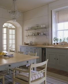 Grand painted blue grey kitchen. l Love the chandelier and the huge arched doors