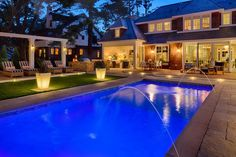 A hanging daybed, outdoor kitchen, beachy outdoor dining area and crystal-clear pool lend this luxurious backyard, designed by Heather Grossman, a resort-like vibe.
