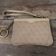Dooney & Bourke wristlet cream Ladies this wristlet has been loved, used and abused. It has a water spot on each side of it and a few small stains on the outside and inside. I have not tried to remove them -see pics for details. Low price bc of these flaws. Dooney & Bourke Bags Clutches & Wristlets