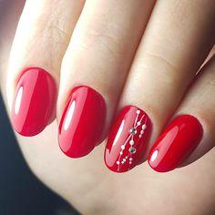 manicure per le feste di natale realizzata con uno smalto gel rosso acceso e una decorazione molto fine sull'anulare