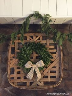Fresh greenery and a boxwood wreath with plaid ribbon bow on a vintage tobacco basket. Makes Christmas decor easy