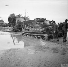 A bulldozer being used to recover a Cromwell tank that became bogged down on the beach, 14 June 1944.