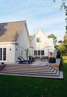 Villa med stor træterrasse med lounge-møbler og have