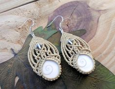 Gorgeous micro macrame earrings with two Shiva Eye shells and natural Crystal Quartz beads set in beige wax thread . The earrings are very light and comfortable to wear , the ear hooks are made of Stamped 925 Sterling Silver .
