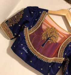 Dazzling deep blue color designer blouse with tree design hand embroidery gold thread and bead work on back of blouse.Ping on 9884179863 to book an appointment. Netted Blouse Designs, Cutwork Blouse Designs, Best Blouse Designs, Simple Blouse Designs, Stylish Blouse Design, Bridal Blouse Designs, Saree Blouse Designs, Sari Blouse, Blouse Neck