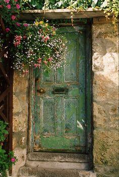 Green door with hanging basket