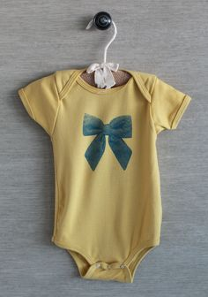 Ribbon In The Sky Onesie 24.99 at shopruche.com. Wonderfully soft and comfortable, this mustard onesie is rendered in an organic cotton knit with a precious blue bow graphic. Completed with ribbed hems and bottom snap closures. Machine washable.100% Organic Cotton, Made in USA