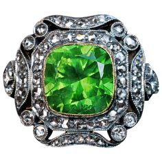 Rare 4 Carat Russian Demantoid silver gold Engagement Ring. A silver topped 14K gold ring features a rare 4.19 ct vivid green Russian demantoid set in an ornate Art Deco frame embellished with numerous rose cut diamonds