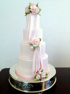 Pink wedding cake with drapery and pink sugar flowers.